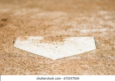Home plate surrounded by dirt on a baseball field