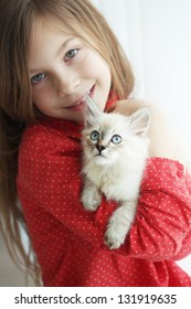 Home portrait of adorable child with small kitten