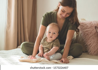Home portrait of a baby boy with mother on the bed. Mom holding and kissing her child. Mother day concept