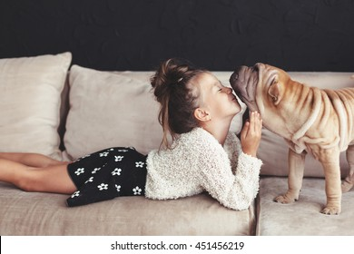 Home portrait of cute child kissing puppy of Chinese Shar Pei dog on the sofa against black wall