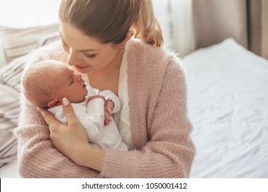 Home portrait of a newborn baby with mother on the bed. Mom holding and kissing her child.