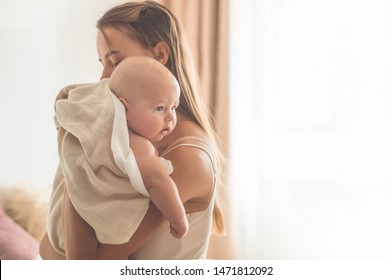 Home portrait of a newborn baby with mother on the bed. Mom holding and kissing her child. Concept breast feeding.
