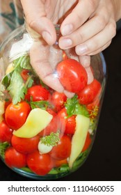 home preserving of tomatoes. the hand settles the tomatoes in a jar for canning for the winter.