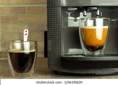 Home professional coffee machine with espresso cup. Coffee preparation. Espresso coffee maker machine and glass with hot coffee.