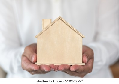 Home property ownership for rent, sale, leasing and safety insurance concept with new house in landloard or real estate realtor hand giving to buyer, renter or tenant