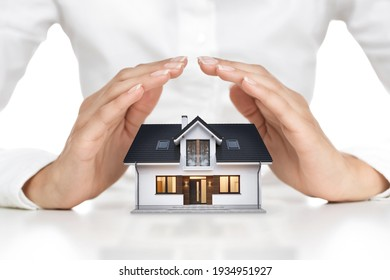 Home protection concept, close up of female hands sheltering modern house
