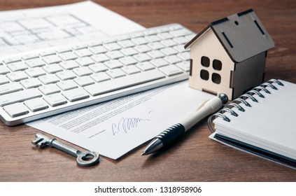 home purchase contract, miniature house, door key, keyboard close up