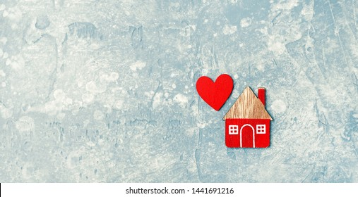 home and red heart on abstract backdrop. Home, symbol of love, family.  Wooden toy house and heart. Concept of cozy, loving, protecting, cozy home. copy space