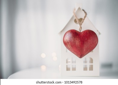 Home and red heart on white background.  concept for St. Valentine's Day and sale of houses