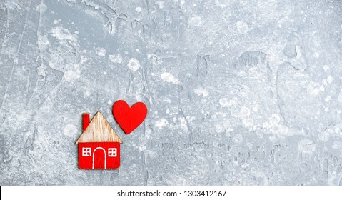 home and red heart, symbol of love, family. design for Valentine's day greetings background. Wooden toy house on grey background. Concept of cozy, loving, protecting, cozy home, care, insurance.