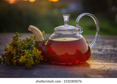 Home remedies for fast flu relief: hot herbal chamomile tea and St. John's wort tea in glass teapot on wooden table