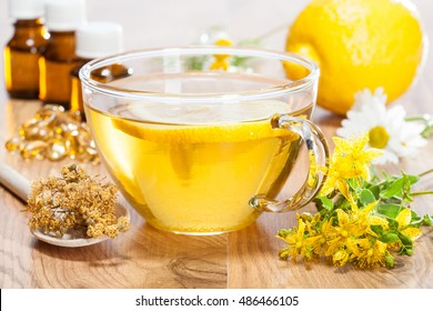 Home remedies for fast flu relief: hot herbal tea, lemon, herbs and bottles with natural infusions on wooden table