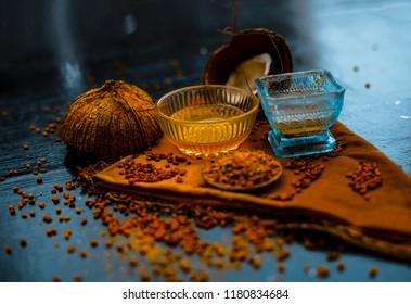 Home remedy to control hair fall i.e. fenugreek seeds or methi seeds or methi dana with coconut oil on wooden surface in glass bottle or bowl with raw coconut and fenugreek,Top shot and close up view.