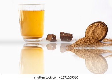 Home remedy to reduce headache or to treat headache isolated on white i.e. Hing or Devil's dung powder well mixed in water with its reflection also.
