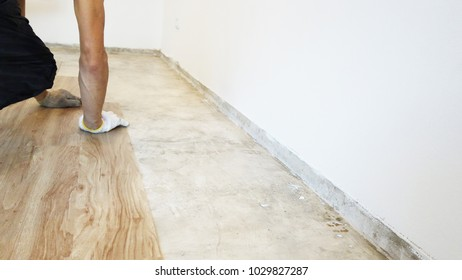 Home renovate with vinyl laminate flooring. Man installing new wooden vinyl laminate flooring
