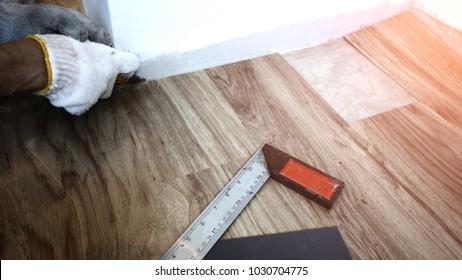 Home renovate with vinyl laminate flooring. Man installing new vinyl laminate floor tile. Man cutting laminate floor.