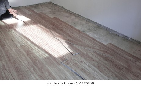 Home renovate with vinyl laminate flooring. Worker installing new wooden vinyl laminate flooring