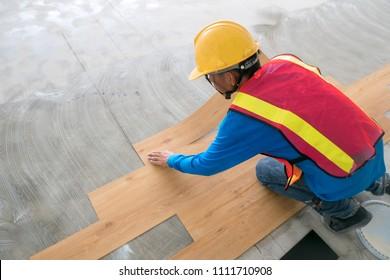 Home renovate with vinyl laminate flooring. construction worker  installing new vinyl laminate floor tile.