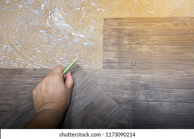 Home renovate with vinyl laminate flooring. Man installing new vinyl laminate floor tile. Man cutting laminate floor.