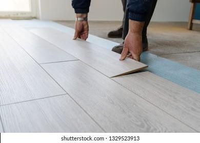 Home renovate with vinyl laminate flooring. Professional construction worker installing new vinyl laminate floor tile
