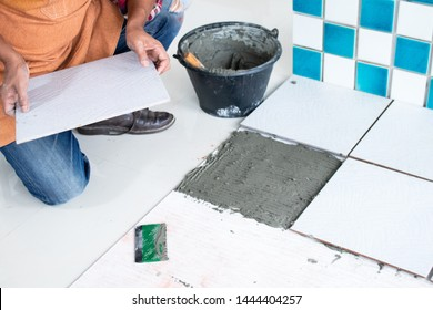 Home renovation and improvement concept. Professional tiler or building contractor preparing tile work by using trowel and cement in site. Renovate or decorate plan for good service and safe budget.