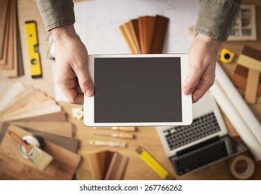 Home renovation and technology concept, male hands holding a digital tablet with work table and tools on background, top view