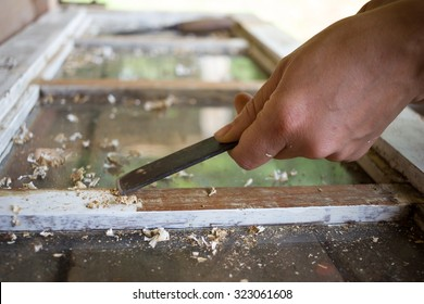 Home Renovation, woman's hand removing a white paint from a wooden Window with a Scraper