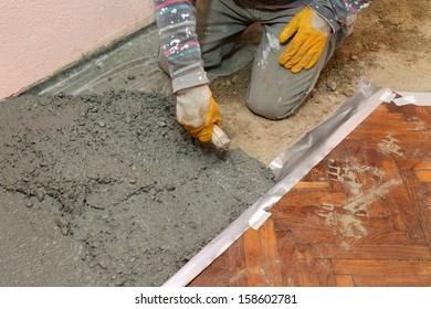 Home renovation, worker finishing concrete with trowel