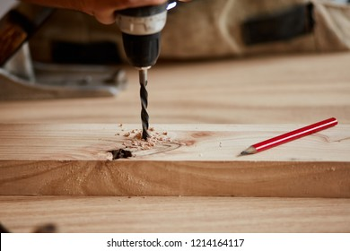 Home repair concepts, close up. Custom-made Furniture Concept. Handicraft Carpentry. Cabinet-maker hands drilling a wooden plank using electric drill on the working table in the workshop.