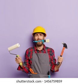 Home repair male worker busy with house renovation, holds building equipment, has sad expression, wears casual working clothes, looks up. Builder with paint roller, brush and hammer stands indoor
