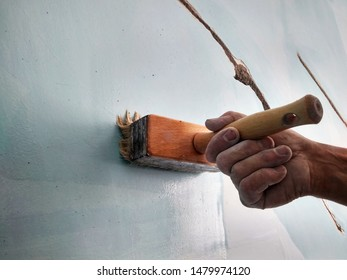 home repair, a man brushes the cracks in the wall before puttying with a brush