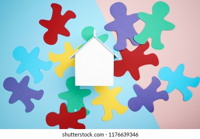 Home replica and colorful people made from color paper on top of pastel background