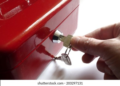 Home safe box with hand turning key in lock.