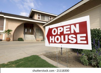 A home for sale shows the open house sign on a sunny afternoon.