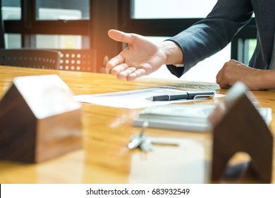 Home sales brokers are offering home sales,pen is placed on the contract document,Model house on the front desk.