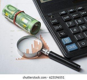 Home savings, budget concept. Chart, magnifying glass, calculator and money on wooden table