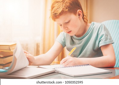 Home schooling, red-haired boy learns writing down in a workbook