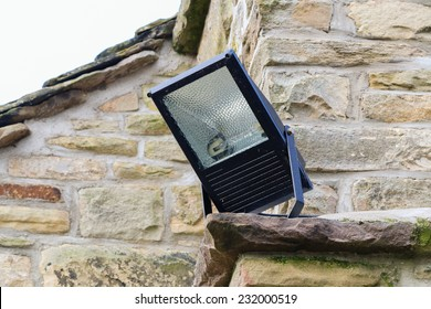 Home security light outdoor on the corner of a stone cottage. Metal halide floodlight enclosure.