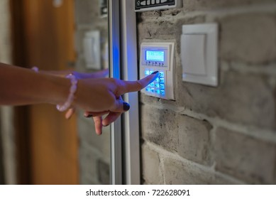 Home security system. Woman entering password on home alarm keypad