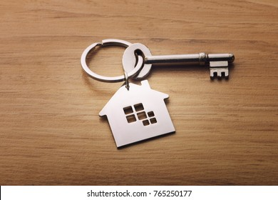 Home shape keychain on wooden background