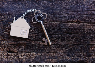 Home shape keyring with antique key on old wooden table. Welcome to new home, home sweet home concept. Copy space.