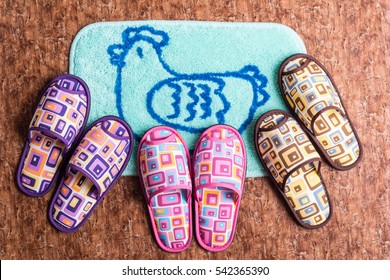 Home slippers on the blue mat with artificial wood flooring background.