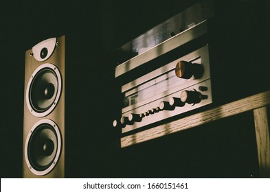 Home sound system - wooden speaker with two white membrane drivers, vintage stereo receiver and turntable placed on the top of it. Audio equipment stands on the wooden shelf. Heavy shadow scene.