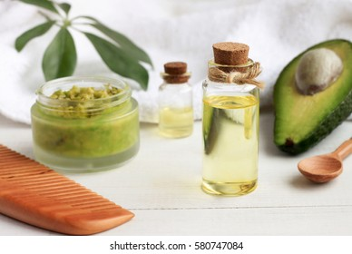Home spa. Avocado oil facial mask, oil in bottle, white and green towels. Natural skincare treatment