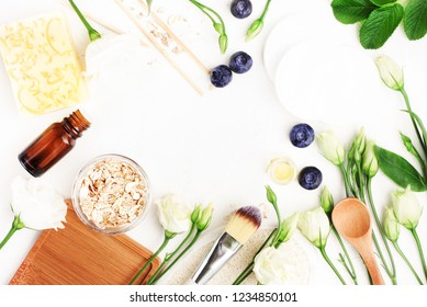Home spa background framed with fresh natural ingredients for beauty & body care. Top view oat flakes, berries, herbal leaves, cosmetic set. Botanical skincare treatment recipe.