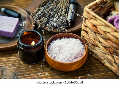 Home spa day with lavender products, top view of spa still life towels, lavender oil, natural soap, bath salt, body brush and scented candle, lavender spa composition