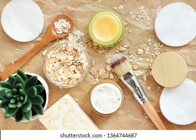 Home spa with natural cosmetics with oat flakes, body butter, facial mask in jar. Beauty treatment ingredients on beige craft paper & plant decor.