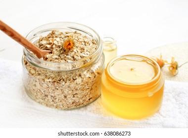 Home spa skincare ingredients. Glass jars of oatmeal flaks and yellow honey, white bathroom towel