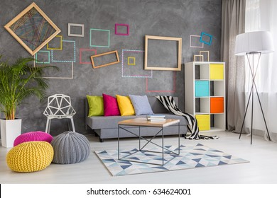 Home space with decorative wall frames, colorful poufs and sofa