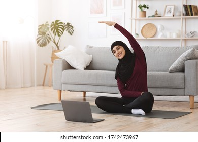 Home sport for muslim women. Smiling arabic girl in hijab practicing online yoga, watching video tutorial on laptop, excersising in living room